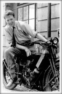 Oliver Smithies in his early twenties, sitting on a motorcycle
